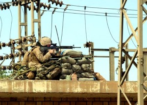 From a rooftop position, Marines with G Company, 2nd Battalion, 1st Marine Regiment, aim at a building from which shots had been fired in Fallujah, Iraq, April 6, 2004. U.S. Marine Corps photo by Lance Cpl. Nathan Alan Heusdens